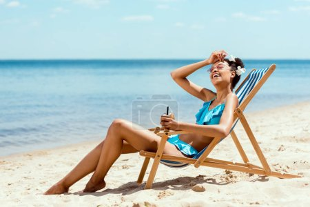 young african american woman in bikini wiping forehead and holding cocktail in coconut shell while laying on deck chair on sandy beach