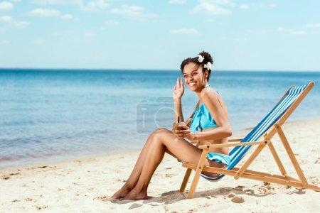 Photo pour Heureuse femme afro-américaine en bikini avec cocktail en coque de noix de coco agitant à la main alors qu'elle était assise sur une chaise longue sur une plage de sable - image libre de droit