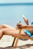 cropped image of woman holding cocktail in coconut shell and using smartphone while laying on deck chair on sandy beach