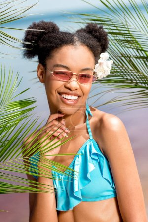 happy african american woman in sunglasses with flower in hair near palm leaves in front of sea