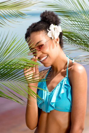 smiling african american woman in sunglasses with flower in hair near palm leaves in front of sea