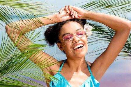 Photo pour Heureuse femme afro-américaine avec de larges bras portant des fleurs dans les cheveux près des feuilles de palmier en face de la mer - image libre de droit