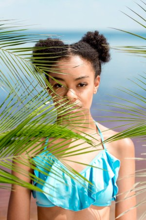 portrait of serious african american woman near palm leaves in front of sea