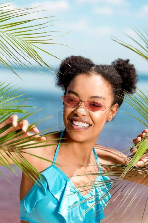 smiling african american woman in sunglasses near palm leaves in front of sea