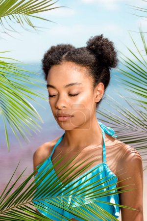 african american woman with closed eyes near palm leaves in front of sea