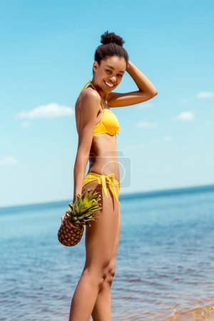 Photo for Happy african american woman in bikini holding pineapple on sandy beach - Royalty Free Image