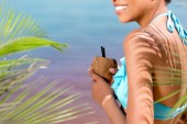 cropped image of smiling woman in swimwear holding cocktail in coconut shell near palm branches in front of sea