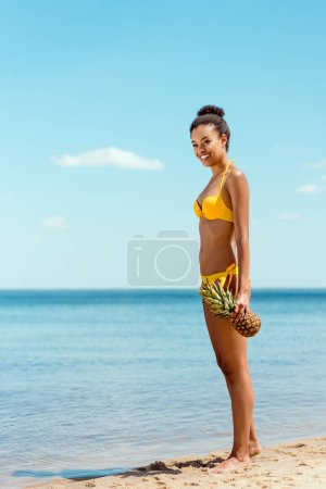 smiling african american woman in bikini holding pineapple on sandy beach