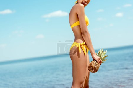 Photo for Cropped image of smiling woman in bikini holding pineapple on sandy beach - Royalty Free Image