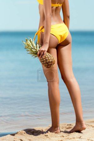 Photo for Cropped image of  woman in bikini holding pineapple on sandy beach - Royalty Free Image