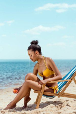 Photo for African american woman applying sunscreen lotion on skin while sitting on deck chair on sandy beach - Royalty Free Image