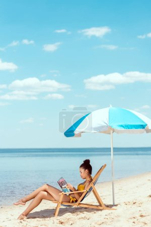 side view of young african american woman reading magazine and relaxing on deck chair under beach umbrella in front sea