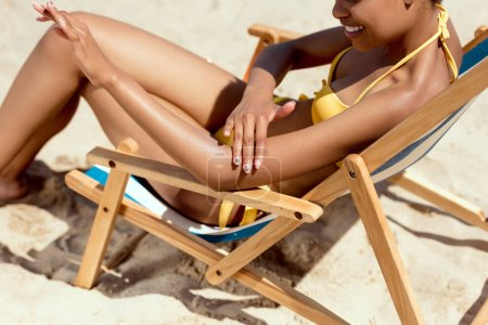 cropped image of young woman applying sunscreen lotion on skin while sitting on deck chair on sandy beach