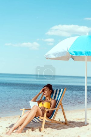 laughing african american woman relaxing on deck chair and using digital tablet under beach umbrella in front of sea