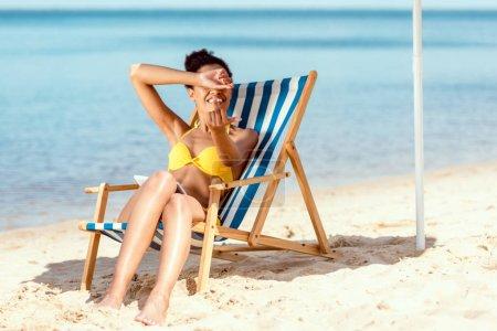 Photo pour Femme souriante couvrant les yeux à la main et montrant le majeur tout en étant allongé sur une chaise longue sur une plage de sable - image libre de droit