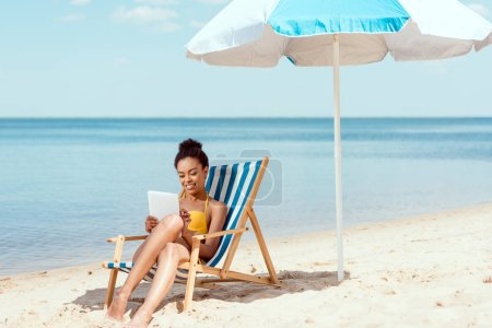 Photo for African american woman relaxing on deck chair and using digital tablet under beach umbrella in front of sea - Royalty Free Image