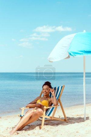 sonriente mujer afroamericana relajándose en la tumbona y escuchando música en auriculares con teléfono inteligente bajo el paraguas de la playa frente al mar