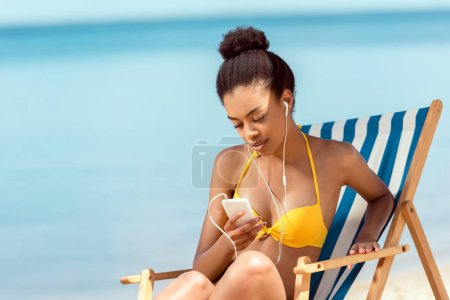 attractive african american woman laying on deck chair and listening music in earphones with smartphone in front of sea