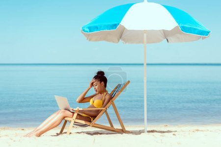 side view of smiling african american female freelancer sitting on deck chair and using laptop under beach umbrella in front of sea