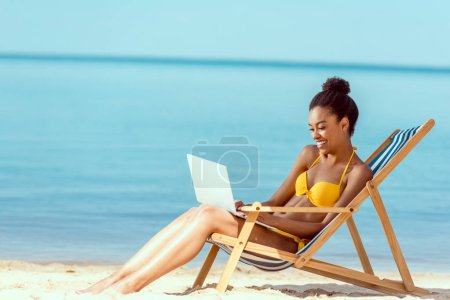 Photo for Smiling african american female freelancer sitting on deck chair and using laptop on sandy beach - Royalty Free Image