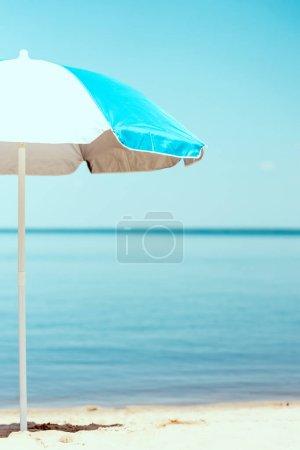 selective focus of beach umbrella in front of sea