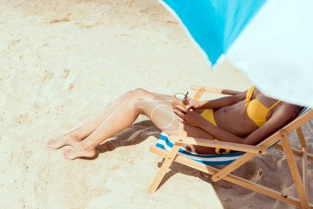 cropped image of woman in bikini laying on deck chair and holding cocktail in coconut shell under beach umbrella on sandy beach