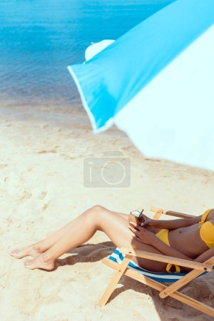 cropped image of woman in bikini laying on deck chair and holding cocktail in coconut shell under beach umbrella in front of sea