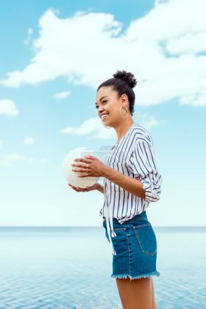low angle view of smiling african american woman holding ball for volleyball in front of sea
