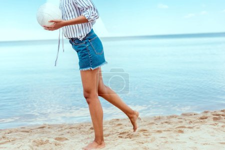 cropped image of woman holding ball for beach volleyball in front of sea