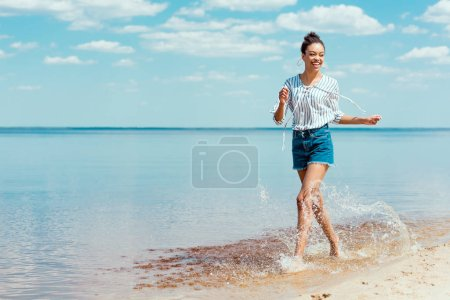 smiling african american woman running in sea water near sandy beach