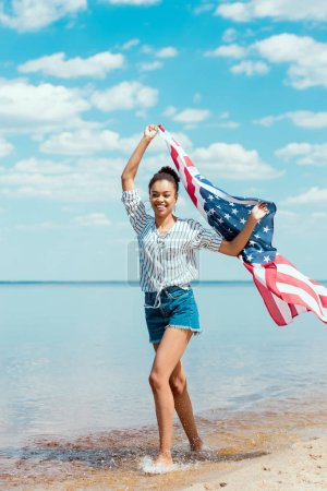 Photo for Smiling african american woman running in sea water with american flag, independence day concept - Royalty Free Image