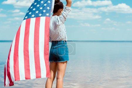 Photo pour Vue arrière du jeune femme tenant le drapeau américain en face de la mer, le concept de la fête de l'indépendance - image libre de droit