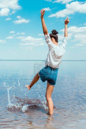 Photo for Rear view of young woman with wide arms kicking sea water - Royalty Free Image