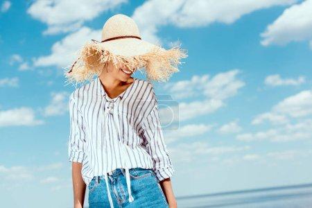 Photo pour Femme afro-américaine souriante en chapeau de paille contre ciel nuageux bleu - image libre de droit