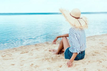 Photo for Rear view of young woman in straw hat relaxing on sandy beach - Royalty Free Image