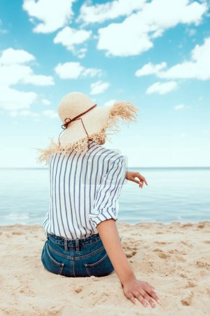 Photo for Rear view of woman in straw hat sitting on sandy beach - Royalty Free Image