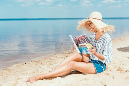 stylish smiling african american woman in straw reading fashion magazine on sandy beach