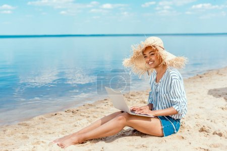 smiling african american female freelancer in straw hat sitting on sandy beach with laptop