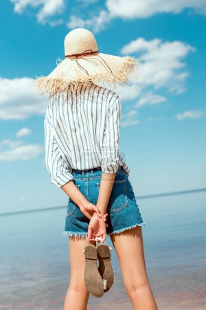 rear view of woman in straw hat holding sandals and looking at sea