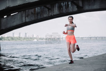 sportswoman looking at smart watch while jogging on quay