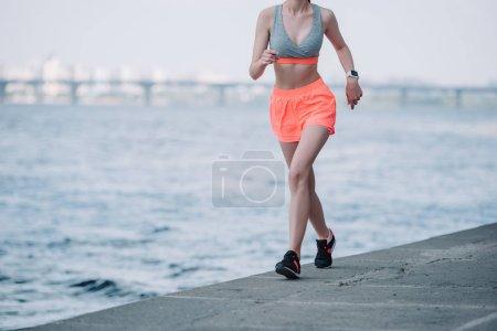 cropped view of sportswoman jogging quay near river