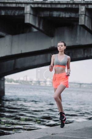 Photo for Attractive sportswoman jogging on quay near bridge - Royalty Free Image
