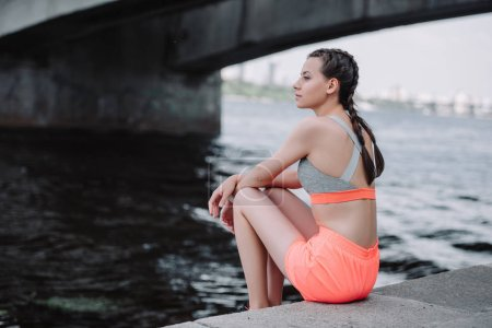 Photo for Attractive young athletic woman in sportswear sitting on quay - Royalty Free Image