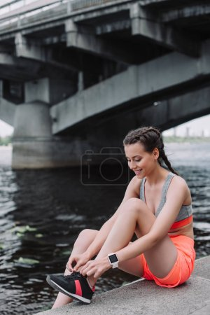 smiling sportswoman tying laces on sneakers and sitting on quay