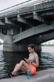 belle sportive en utilisant smartphone avec écouteurs et montre intelligente tout en étant assis sur le quai près du pont