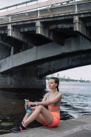 Photo pour Jeune sportive avec une bouteille de smartwatch et de sports avec de l'eau, assis sur le quai près de la rivière - image libre de droit