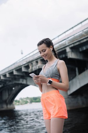 beautiful young sportswoman using smartphone with earphones and smartwatch