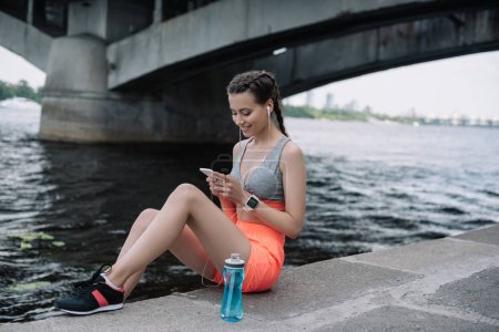 young sportswoman using smartphone with earphones and smart watch
