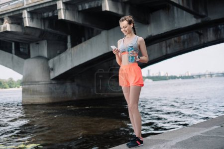 Photo for Young sportswoman holding smartphone and bottle with water - Royalty Free Image