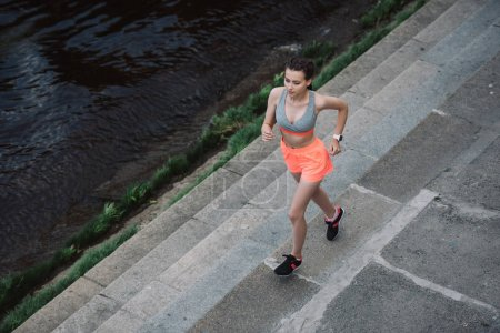 overhead view of young female jogger running in city